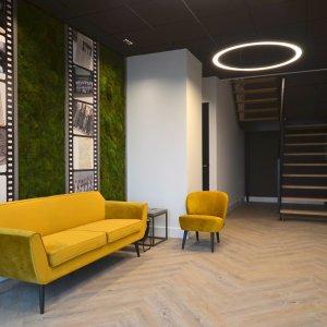 Dit is een interieur met een moswand en een Washingtonia palm. De GroenStyliste van StudioCentro komt graag naar je toe om deze kantoorplanten te plaatsen.
